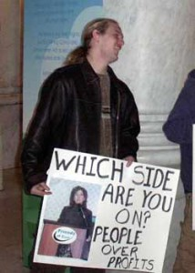 """This photo by Abe Mwaura from 2005 illustrates the problem.  Back then, we captioned the photo, """"Who does she work for, anyway? Scott Straights poster includes a picture of DEP chief Timmermeyer speaking at a Friends of Coal meeting. This photo was featured on the DEP website's home page."""""""