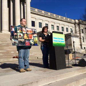 Paula at podium, Dustin with sign. Photo by Janet Keating.
