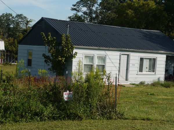 """A home at compressor's fenceline. The weed-covered sign reads """"No Trespassing / No Smoking""""."""