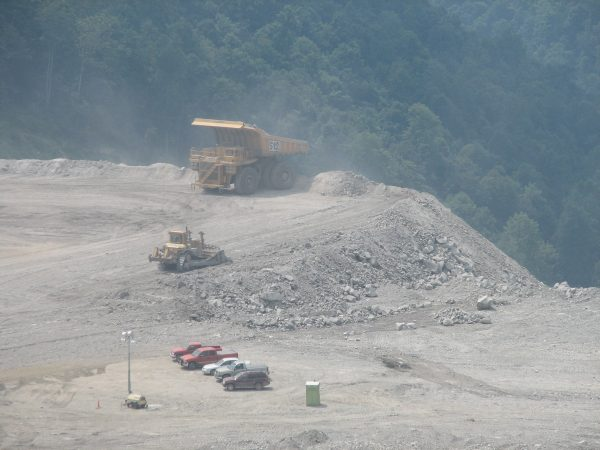 A huge dump truck about dump its load of former mountain into a valley. Photo by Vivian Stockman.
