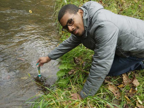Above: Charles Orgbon, III, checks the conductivity  of a MTR-impacted stream in Boone County, WV.