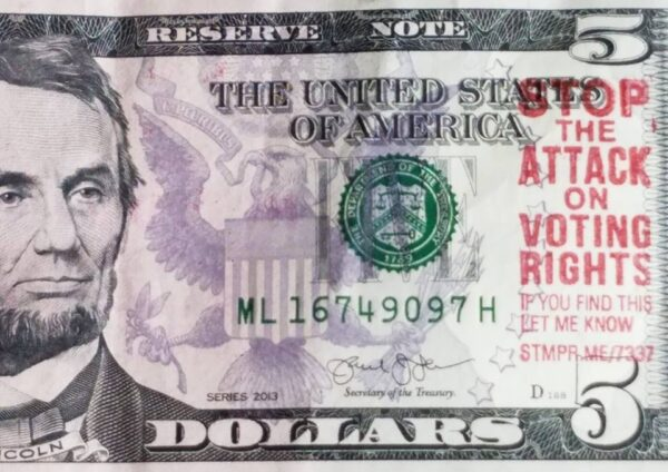 "Photo of five dollar bill stamped with ""Stop the attack on voting rights"""